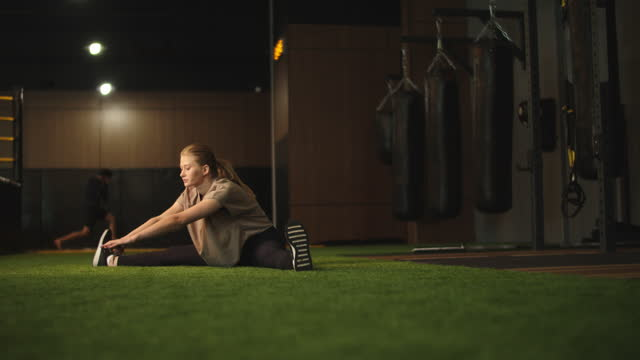 vídeos de stock e filmes b-roll de energetic sport woman doing splits in sport club. fit girl warming up at gym - box separate life