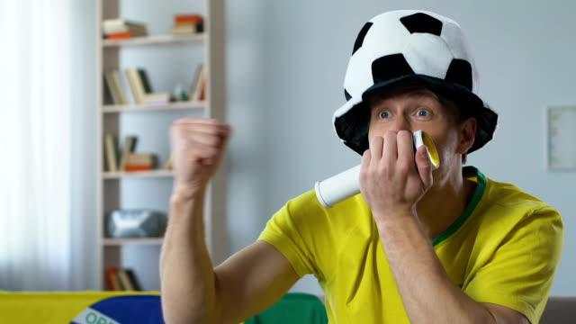 Enérgico defensor do Brasil com chifre fã assistindo jogo, comemorando gol - vídeo