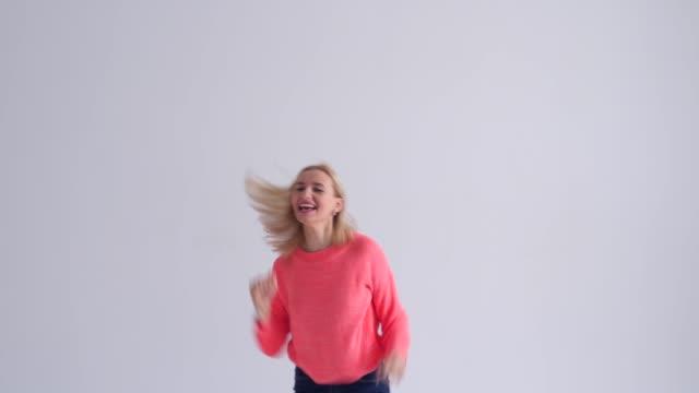 energetic woman jumping giving thumb up - znak ok filmów i materiałów b-roll
