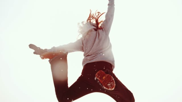 Energetic woman jumping, kicking up snow against sunny sky, super slow motion