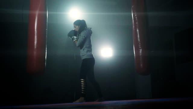 energetic woman kickboxing - sacco per il pugilato video stock e b–roll
