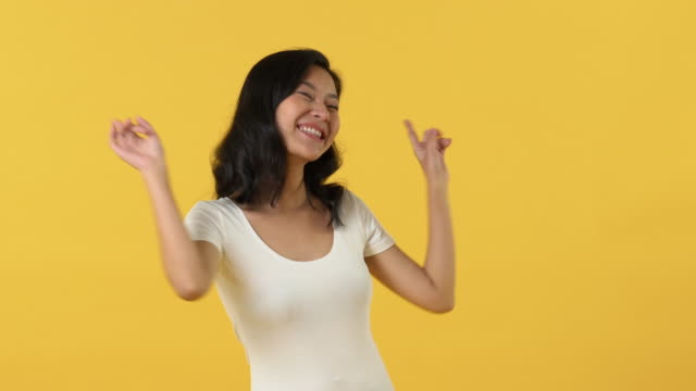 Energetic young Asian woman smiling and dancing Energetic happy young Asian woman smiling and dancing against yellow background background color stock videos & royalty-free footage