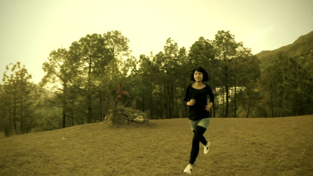 Energetic young woman walking and jogging in fresh air. video