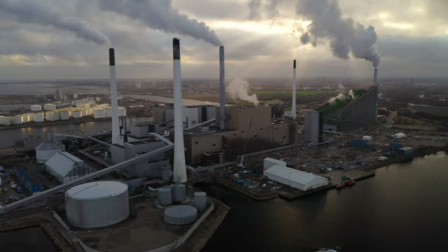 energy plant Aerial 4K shot of energy plant driven by sustainable biomass in Copenhagen, Denmark. This fossil free energy system, fueled biomass, a renewable energy source plays a central role in district heating in the capital area. Aerial view shot with drone biomass renewable energy source stock videos & royalty-free footage