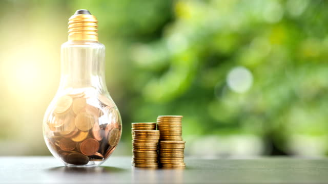 Energy saving. stacks of coins in light bulb and Motion tree nature background. Saving, accounting and financial concept. video 4K Slow motion