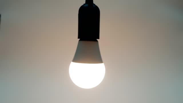 energiesparende, umweltfreundliche led-lampenlampen leuchten an, schwankend auf dem draht - led leuchtmittel stock-videos und b-roll-filmmaterial