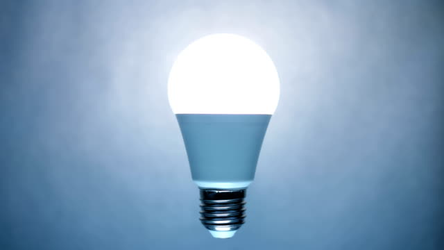 energiesparende, umweltfreundliche led-lampenlampe leuchtet auf einem hellen hintergrund - led leuchtmittel stock-videos und b-roll-filmmaterial