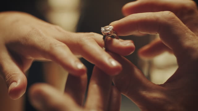 Engagement ring A couple sitting at a dining table. The man presenting his girlfriend an engagement ring.   love emotion stock videos & royalty-free footage