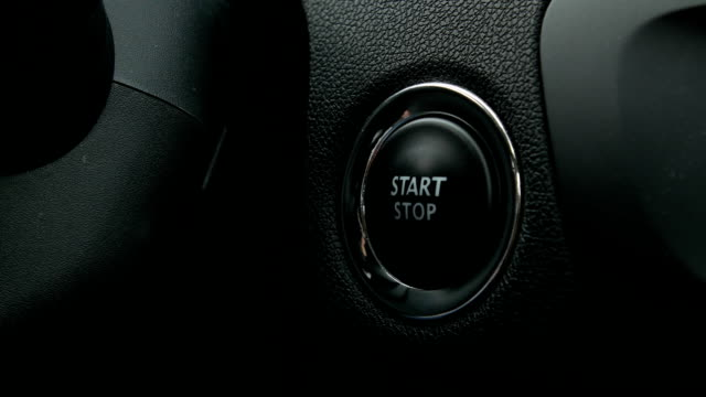 Engine start stop button from a modern car interior Pushing engine start stop button from a modern car interior. power supply stock videos & royalty-free footage