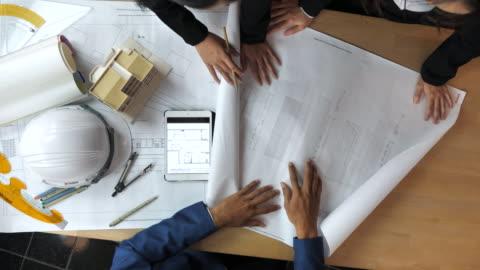 vidéos et rushes de ingénieur et architecte équipe regardent blueprint, slow motion - architecte