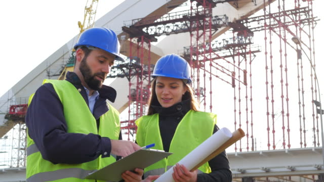Engineer and architect with blueprints on construction site Two people male engineer and female architect discussing construction progress near the construction frame and bridge building site, looking at blueprints and documents. Footage taken in 4K resolution in Central Europe. civil engineering stock videos & royalty-free footage