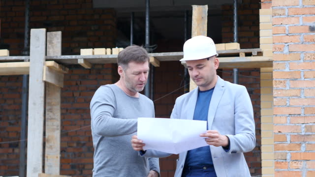vídeos de stock e filmes b-roll de engineer and client looking on project on the construction site - trabalho de design