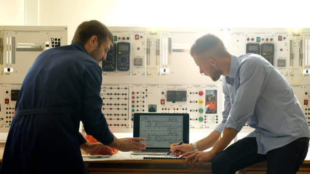 engineer and foreman working at control room of a modern thermal power plant - centrale elettrica video stock e b–roll
