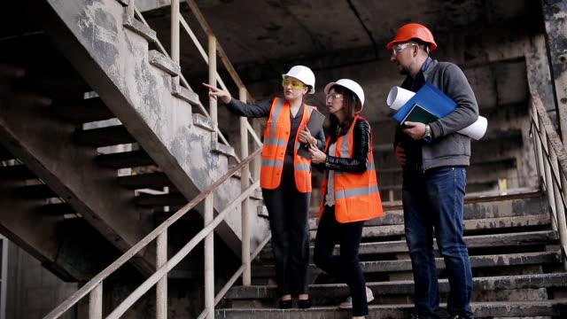 engineer and two women inspectors on-site construction or restoration site inspect stairwells and discuss the details of the construction or reconstruction. - sprawdzać filmów i materiałów b-roll