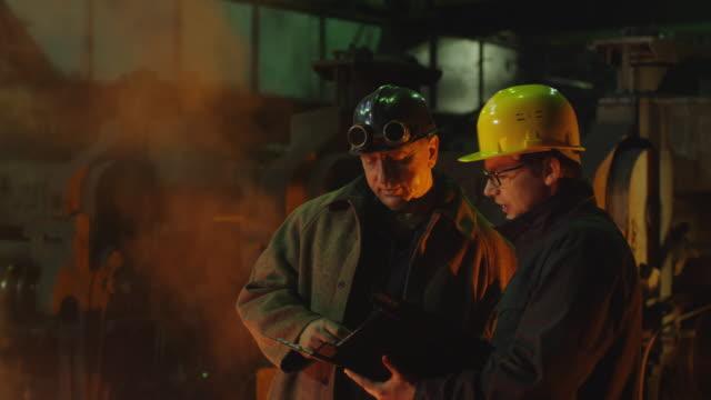 ingenjör och arbetare har konversation i foundry. ingenjör använda tablet. grov industriell miljö. - metallindustri bildbanksvideor och videomaterial från bakom kulisserna