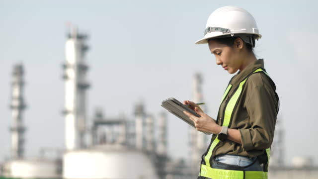 Engineer Asian Worker at industrial plant working on a Digital tablet
