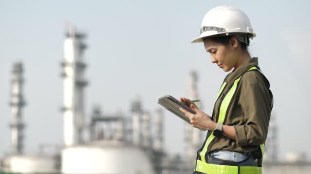vidéos et rushes de ouvrier asiatique d'ingénieur à l'usine industrielle travaillant sur une tablette numérique - inspecteur