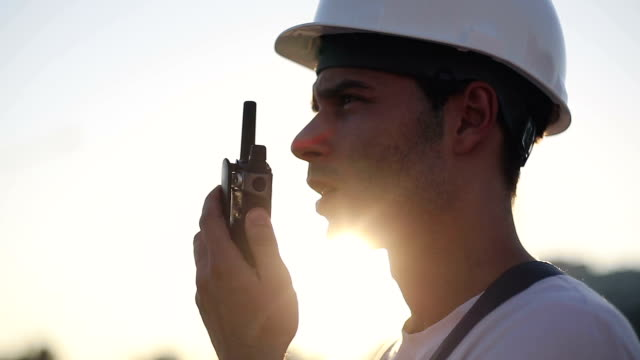 Engineer builder using a walkie talkie giving instructions video