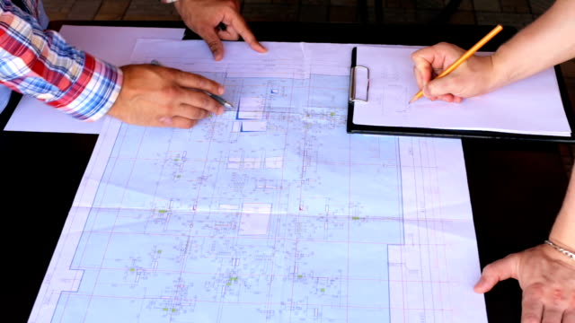 Engineer builders are checking the drawing of a tall house - vídeo
