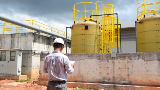 Engineer checking water treatment plant with blueprint