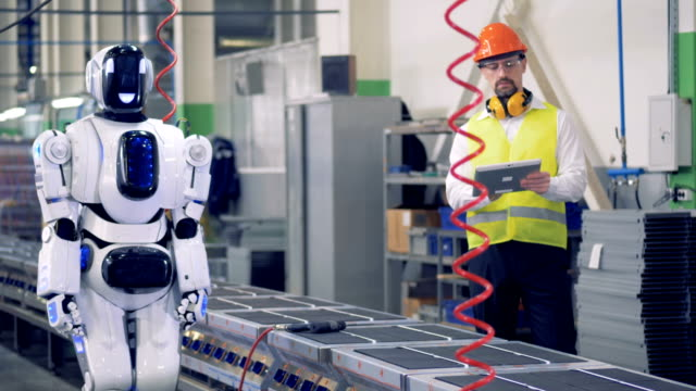 Engineer controls robot working at a conveyor in a factory. 4K. video
