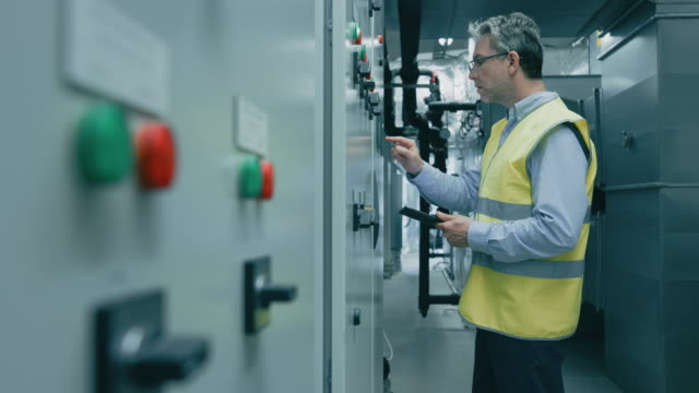 engineer / factory worker programming / setting up machinery on a power station. - centrale elettrica video stock e b–roll