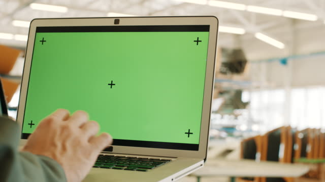 Engineer holding laptop with green screen chroma key