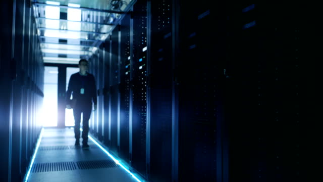 IT Engineer Holding Notebook and Walking Through Data Center Full of Working Rack Servers. video