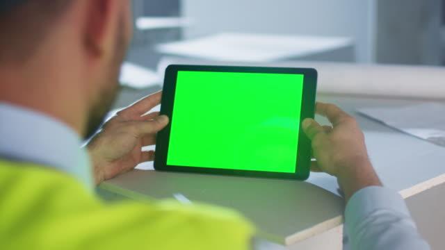 ingenjör holding tablet pc med grön skärm inuti building under uppbyggnad. perfekt för mockup användning. - man architect computer bildbanksvideor och videomaterial från bakom kulisserna
