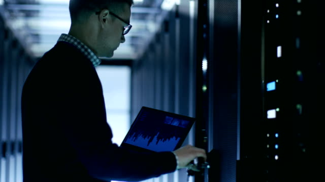 it engineer holds notebook with diagrams on its screen and open server cabinet. - supporto tecnico video stock e b–roll