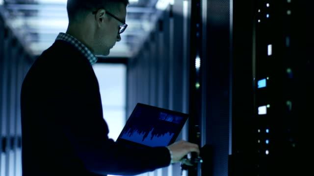 vidéos et rushes de it engineer détient notebook avec des diagrammes sur son écran et open server cabinet. - informatique en nuage