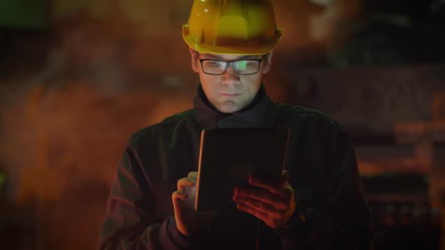 ingenjör i glas med hjälp av tablet pc i gjuteri. industriell miljö. - metallindustri bildbanksvideor och videomaterial från bakom kulisserna