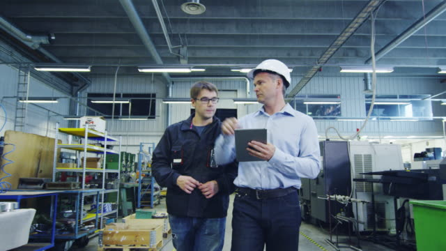 vidéos et rushes de ingénieur en hard hat et factory worker marchent à travers l'installation de production - manager