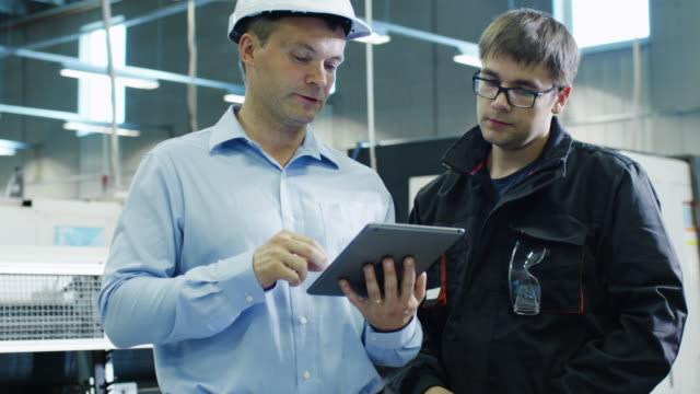 ingenieur in harthut und fabrikarbeiter nutzt tablet-pc auf produktionsanlage - bauarbeiterhelm stock-videos und b-roll-filmmaterial