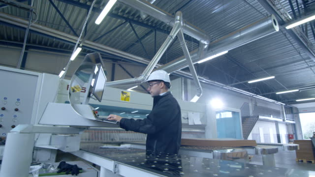 Engineer in Hard Hat Setting Up CNC Machine at the Factory Engineer in Hard Hat Setting Up CNC Machine at the Factory. Shot on RED Cinema Camera 4K (UHD). metal worker stock videos & royalty-free footage