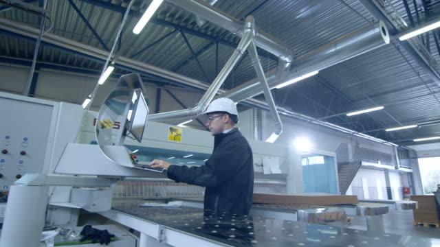stockvideo's en b-roll-footage met ingenieur in hard hat opzetten cnc machine in de fabriek - metaalbewerking