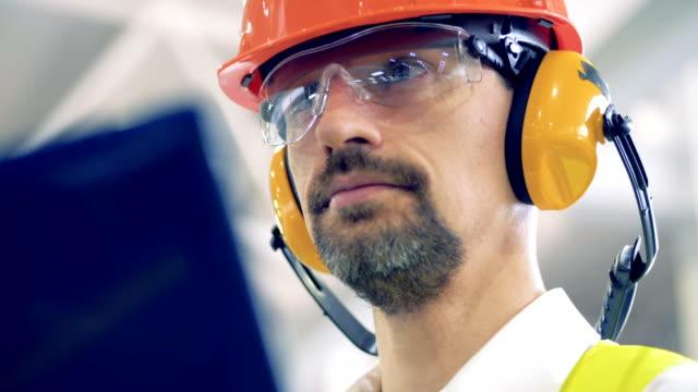 vidéos et rushes de ingénieur en casque travaille sur son ordinateur portable dans un entrepôt, de près. - inspecteur