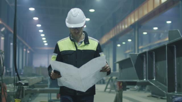 ingenieur in bauarbeiterhelm bewegt sich durch eine schwerindustrie-fabrik mit einer blaupause. - halle gebäude stock-videos und b-roll-filmmaterial