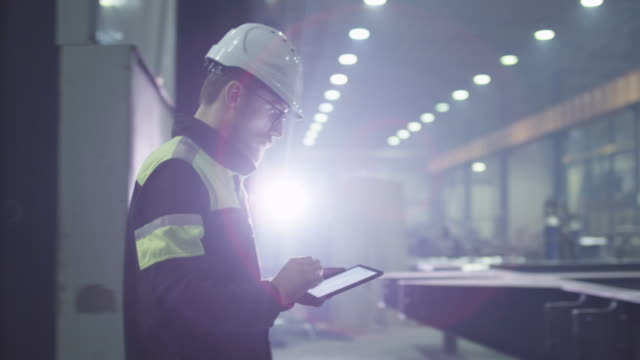 Engineer in hardhat is moving through a heavy industry factory with a tablet computer. Is greeting a worker with a handshake.
