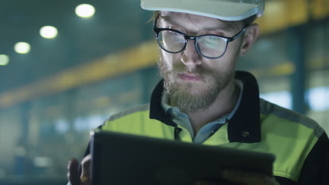 Engineer in hardhat is using a tablet computer in a heavy industry factory. Engineer in hardhat is using a tablet computer in a heavy industry factory. construction equipment stock videos & royalty-free footage
