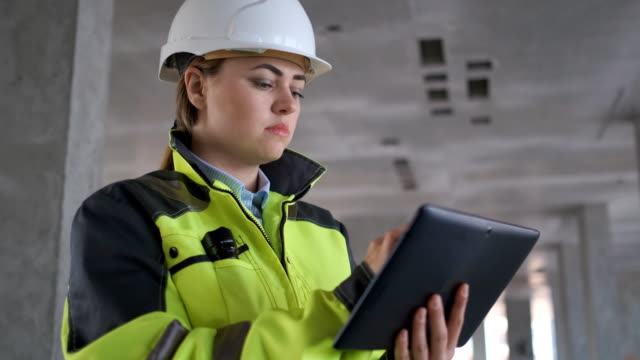ingenjör i hjälmar med tablet-enhet och stora pappersritningar diskuterar - kvinna ventilationssystem bildbanksvideor och videomaterial från bakom kulisserna