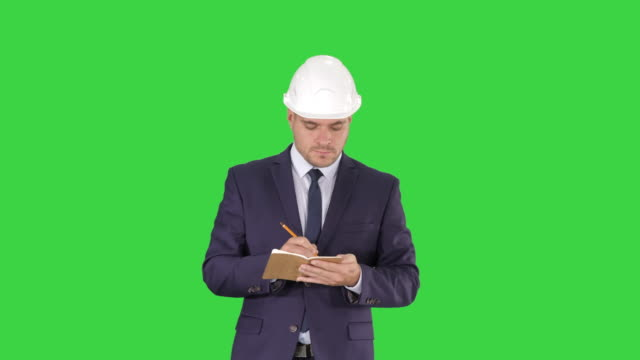 Engineer in suit and helmet walking and writing notes in notepad on a Green Screen, Chroma Key