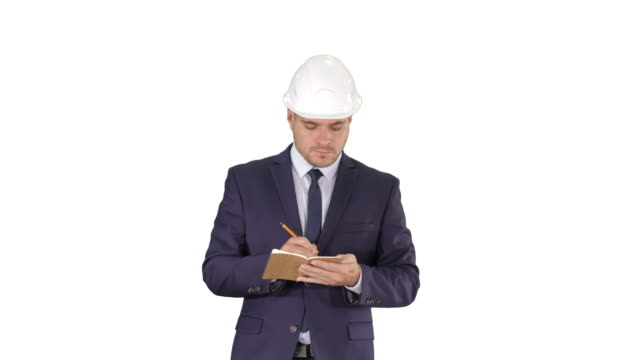 Engineer in suit and helmet walking and writing notes in notepad on white background