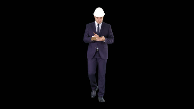 Engineer in suit and helmet walking and writing notes in notepad, Alpha Channel