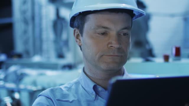 Engineer in Using Tablet in Factory Engineer in Using Tablet in Factory. Shot on RED Cinema Camera in 4K (UHD) metal worker stock videos & royalty-free footage