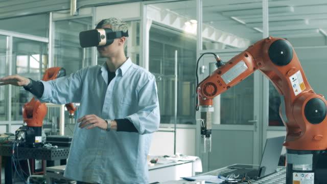 ingenieur in vr-brille manipuliert ein bionisches gerät. gymnasiasten studieren robotik-technologien im universitätslabor. - fortschritt stock-videos und b-roll-filmmaterial