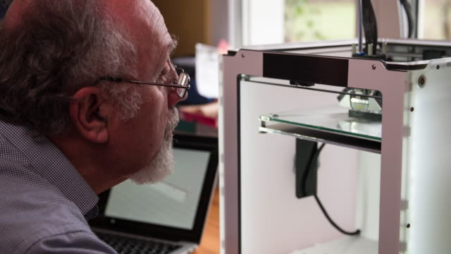 Engineer inspecting 3d Printer video