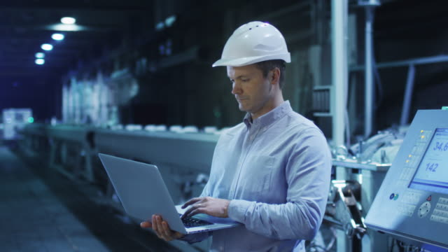 Engineer is Using Laptop in Industrial Environment. Engineer is Using Laptop in Industrial Environment. Shot on RED Cinema Camera in 4K (UHD) quality control stock videos & royalty-free footage