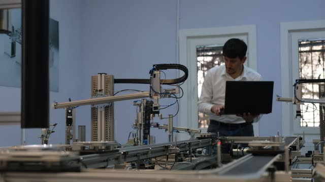 Engineer is working on laptop to program smart factory prototype's automation.