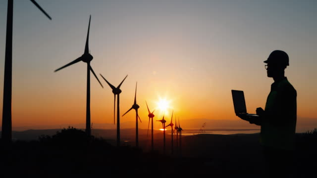 engineer man using computer in wind turbine farm at sunset - sustainability video stock e b–roll